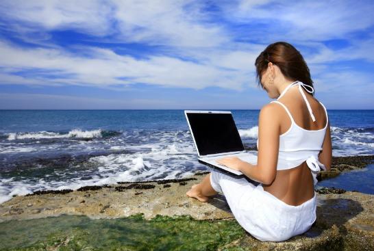 Kvinna med bärbar dator vid vattnet